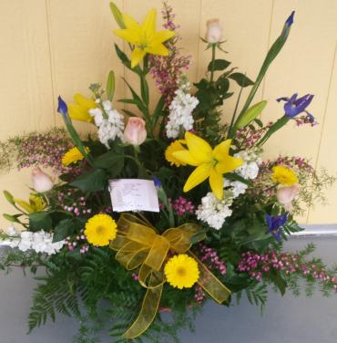 lilies, stock, irises, gerbers, and roses in a wicker basekt