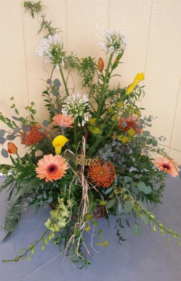 protea, calla lilies, orchids, and gerbers in a wicker basket